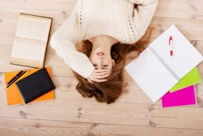 Donna stressata distesa sul pavimento tra i libri