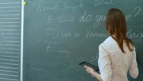 Ragazza che svolge un esercizio di lingua inglese alla lavagna.