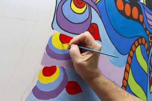 Uomo che disegna un murale.
