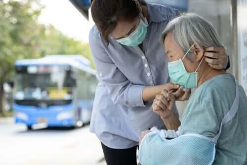 Donna che mette la mascherina a un'anziana.