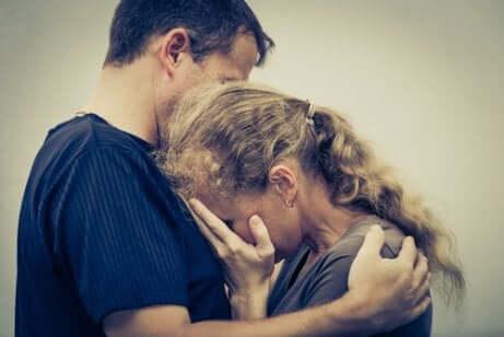 Donna che piange sul petto di un uomo