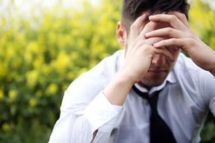 Uomo stressato con le mani sugli occhi.