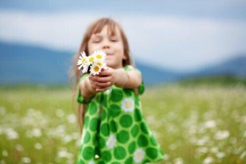 Bambina con fiori in mano.