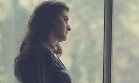 Donna alla finestra che riflette sul nuovo ecosistema del lavoro.