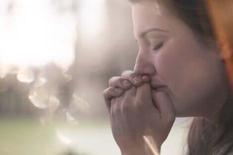 Donna ansiosa si preme le mani sulla bocca.