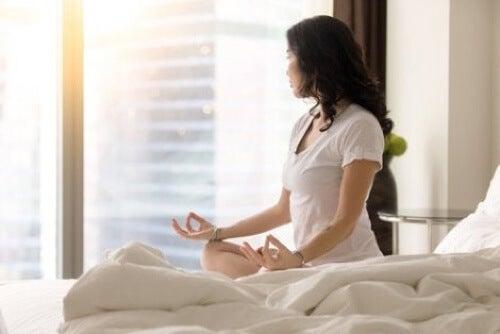 Donna che medita sul letto.