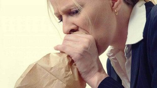 Donna con iperventilazione e ansia che soffia in un sacchetto.