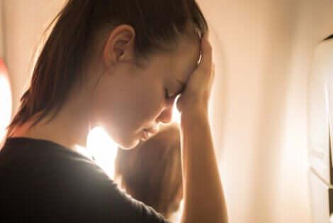 Donna con la testa tra le mani afflitta dalle distorsioni cognitive.