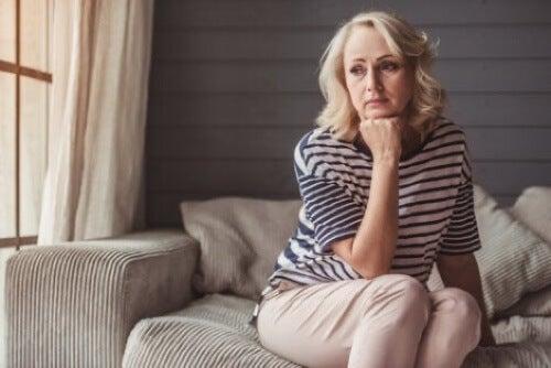 Donna preoccupata seduta sul divano.