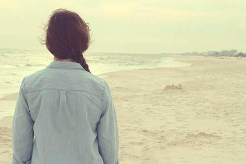 Donna di spalle in spiaggia.