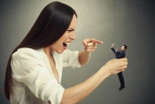 Donna narcisista che punta il dito contro un uomo.