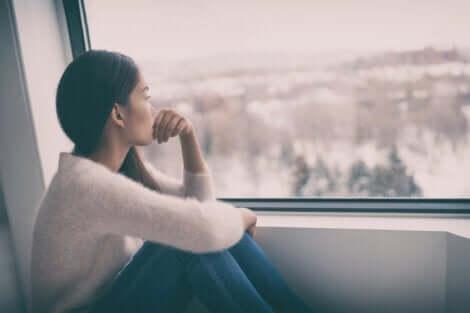 Donna seduta davanti alla finestra.