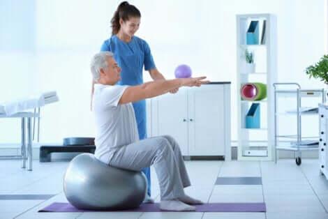 Fisioterapista e paziente anziano.