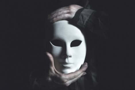 Mani che sorreggono una maschera.