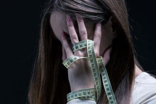 Ragazza anoressica si misura con un metro.