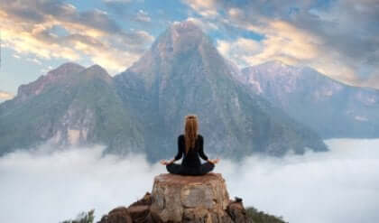Ragazza in posizione yoga medita in cima a una montagna.