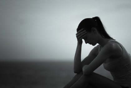 Ragazza seduta con la testa fra le mani ripensa alle relazioni che fanno perdere tempo.