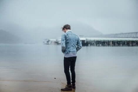 Ragazzo girato di spalle davanti al mare.