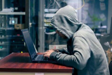 Uomo con cappuccio al computer che sfrutta la psicologia del phishing.