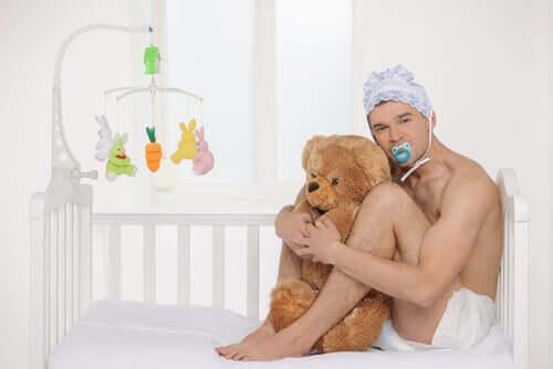 Uomo con cuffia e ciuccio nella culla che abbraccia un orsacchiotto.