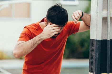 Uomo con mano sulla fronte per la incontinenza urinaria da urgenza.
