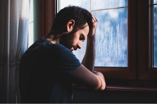 Uomo disperato davanti alla finestra.