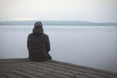 Uomo seduto davanti a un lago.