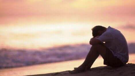 Uomo triste seduto di fronte al mare.