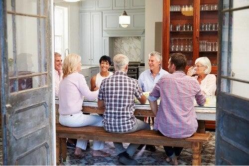 Gruppo di amici adulti seduti a un tavolo.