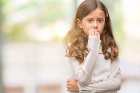 Bambina preoccupata che si mangia le unghie.