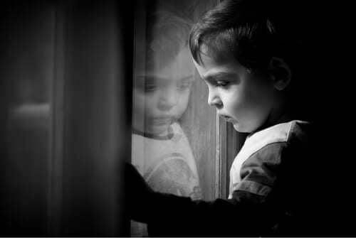 Bambino triste che guarda fuori dalla finestra.