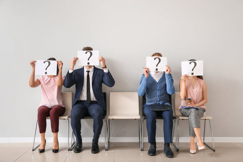 Persone con cartelli con il punto interrogativo sul viso.