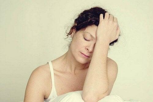 Donna con mal di testa e stanchezza.