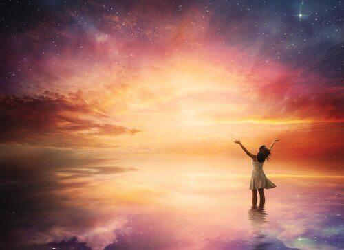 Donna felice che apre le braccia verso il cielo.