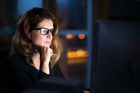 Donna con gli occhiali guarda il monitor del pc.