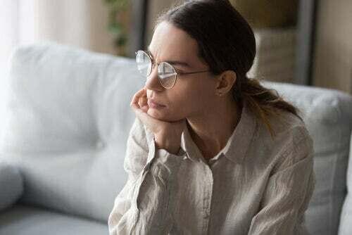 Donna che pensa seduta sul divano.