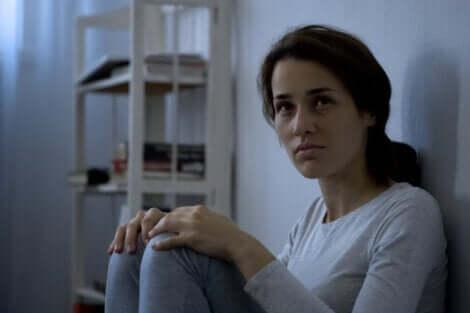 Donna in pigiama seduta per terra.