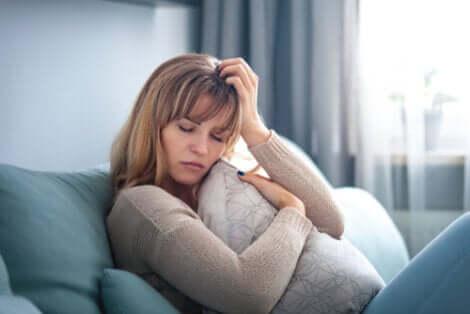 Donna triste seduta sul divano con gli occhi chiusi.