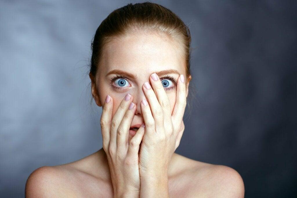 Donna terrorizzata con mani sul viso.