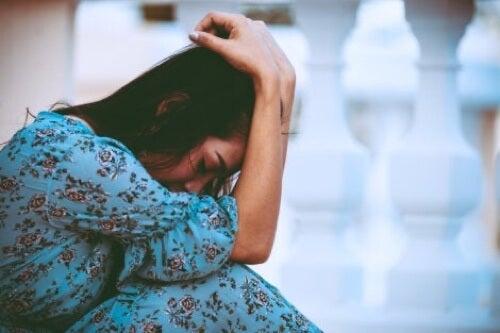 Donna triste con mani sulla testa.