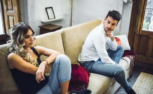 Coppia seduta sul divano con problemi di comunicazione.