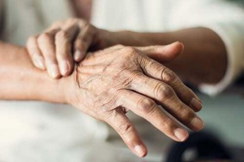 Mani di persona anziana che tremano.