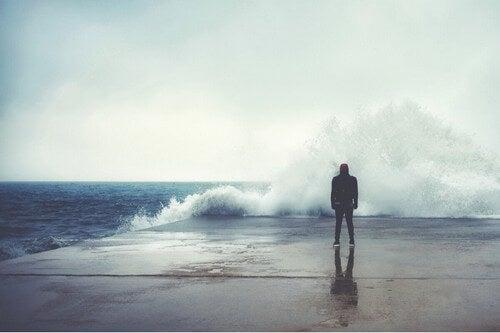 Uomo davanti al mare in tempesta.
