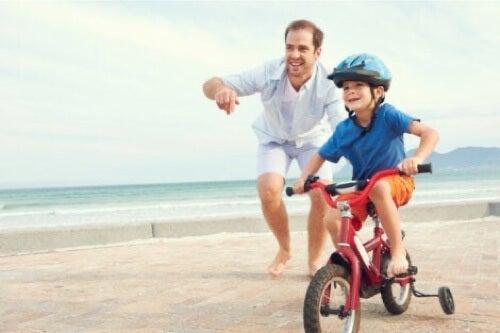 Padre che gioca con il figlio in bicicletta.