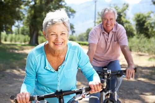 Coppia di persone anziane che fanno un giro in bicicletta in campagna.