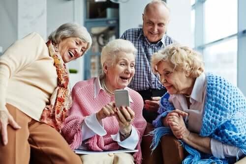 Persone anziane che ridono e si divertono guardando delle foto sul telefono.