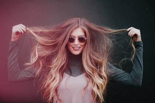 Giovane donna con occhiali che si tocca i lunghi capelli.