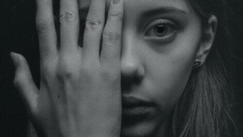 Donna che copre il viso con una mano.