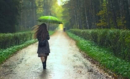 Ragazza cammina sotto la pioggia con un ombrello verde.