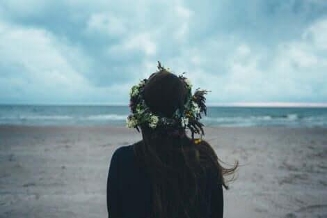 Ragazza di spalle guarda il mare sulla spiaggia.